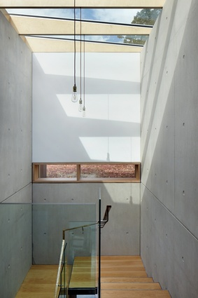 The main staircase features a skylight and double-height exposed concrete walls, making for a dramatic vertical transition from ground floor to upper level.