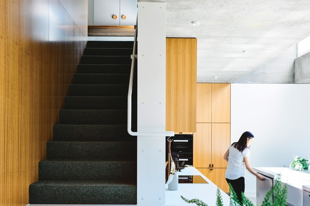 The stairway, tucked neatly between the kitchen and bathrooms, leads up to a study and additional bedrooms.
