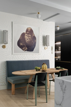 An Enzo Mari gorilla print, with sconces by Erich Ginder on either side, hangs above the kitchen table.