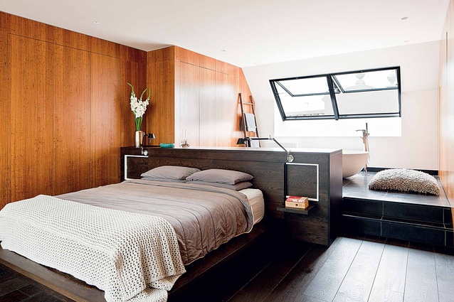 In the master bedroom, timber lined walls impress the clubby, warm aesthetic.