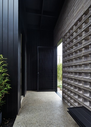 The front door is set within a portico behind a black steel gate and hollow concrete blocks.