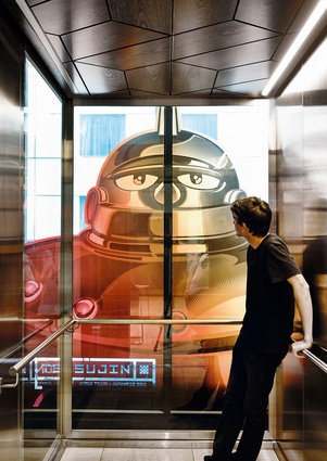 A mural of the Ironman character Tetsujin forms a powerful backdrop in the elevator.