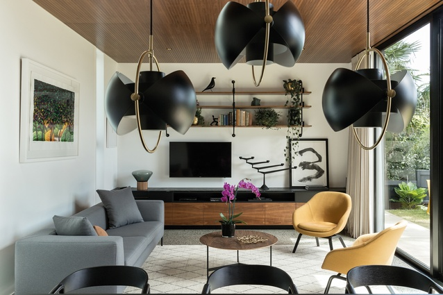 """The double-height, main living room is full of walnut accents, such as the <a  href=""""https://simonjames.co.nz/""""style=""""color:#3386FF""""target=""""_blank""""><u>Simon James</u></a> coffee table. There are also foliage-inspired artworks, such as the Karl Maughan piece (pictured left), and amber-coloured armchairs from <a  href=""""https://cultdesign.co.nz/shop/about-a-lounge-aal82-aal92""""style=""""color:#3386FF""""target=""""_blank""""><u>Cult</u></a>. The amber colour is a nod to the owner/designer's ancestry."""