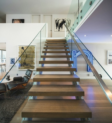 A 'floating' staircase punctuates the double-height space leading to the bedrooms and the mezzanine lounge.