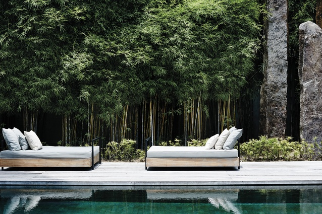 Bamboo lines the pool, along with monolithic stone sculptures. Day-bed cushions are from 