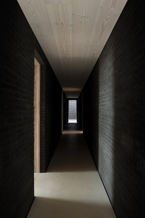 A dark corridor made of black stone.