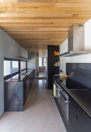 The kitchen's palette is kept simple, consisting of timber, steel, black laminate and concrete.