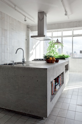The elegant line of the furniture and the warmth of wood are contrasted with a Modernist materiality of concrete, steel and glass in the kitchen.