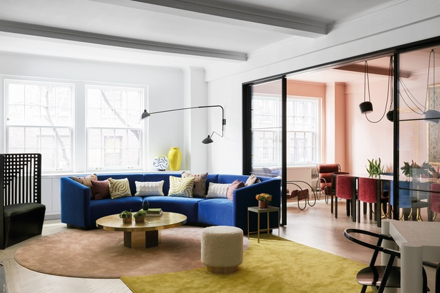 A circular custom sofa, designed by MKCA and upholstered in a blue textile from Maharam, curves around the living room.