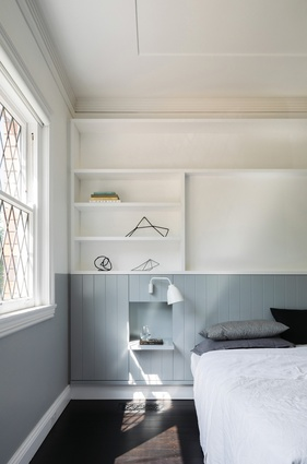 The bedroom features wood-panelled joinery in a warm blue-grey, referencing the panelling in the living area.