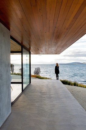 """While the house """"floats"""" on the land's edge, the solid materials lend a grounded feeling."""