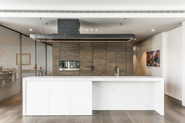 This large, modern kitchen features Fisher & Paykel appliances that accentuate the kitchen's strong architectural form and boldness of the design.