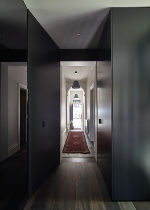 The transition between old and new is marked by a change in wall colour, from light to dark.
