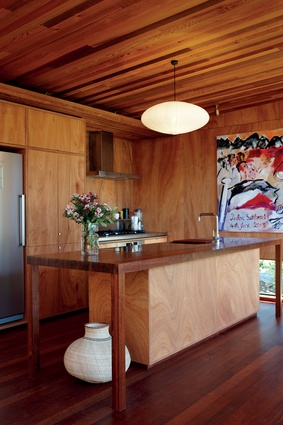 Cedar battens on the ceiling of the kitchen continue from the deck area, while gaboon ply has been used on the walls and for the kitchen cabinetry.