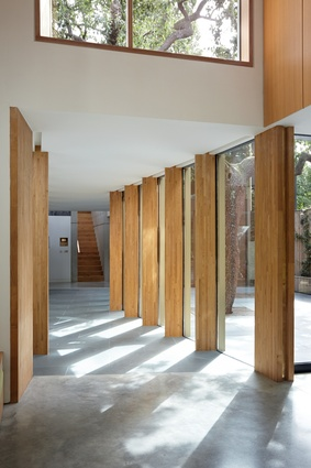 Timber support columns provide framed views of the courtyard.
