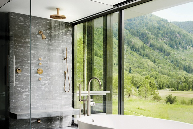 Copper shower and bath fittings add warmth to this outdoor-style space.